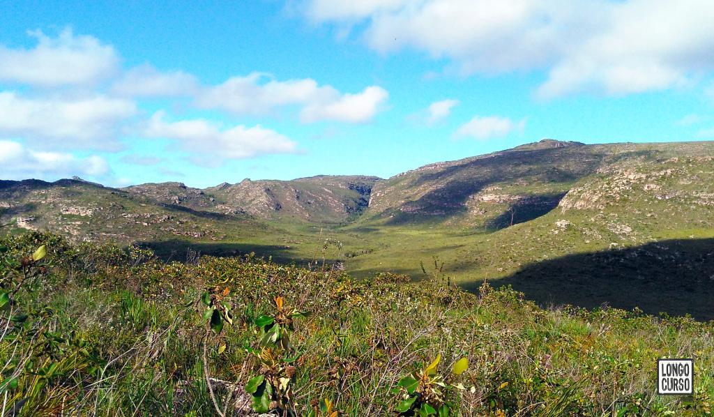 Montanhas ao oeste, no vale do Mucugê. Bem ao centro é possível notar a fenda onde se encontra a nascente do Mucugê. No terreno à sua frente, o leito do rio segue serpenteando.