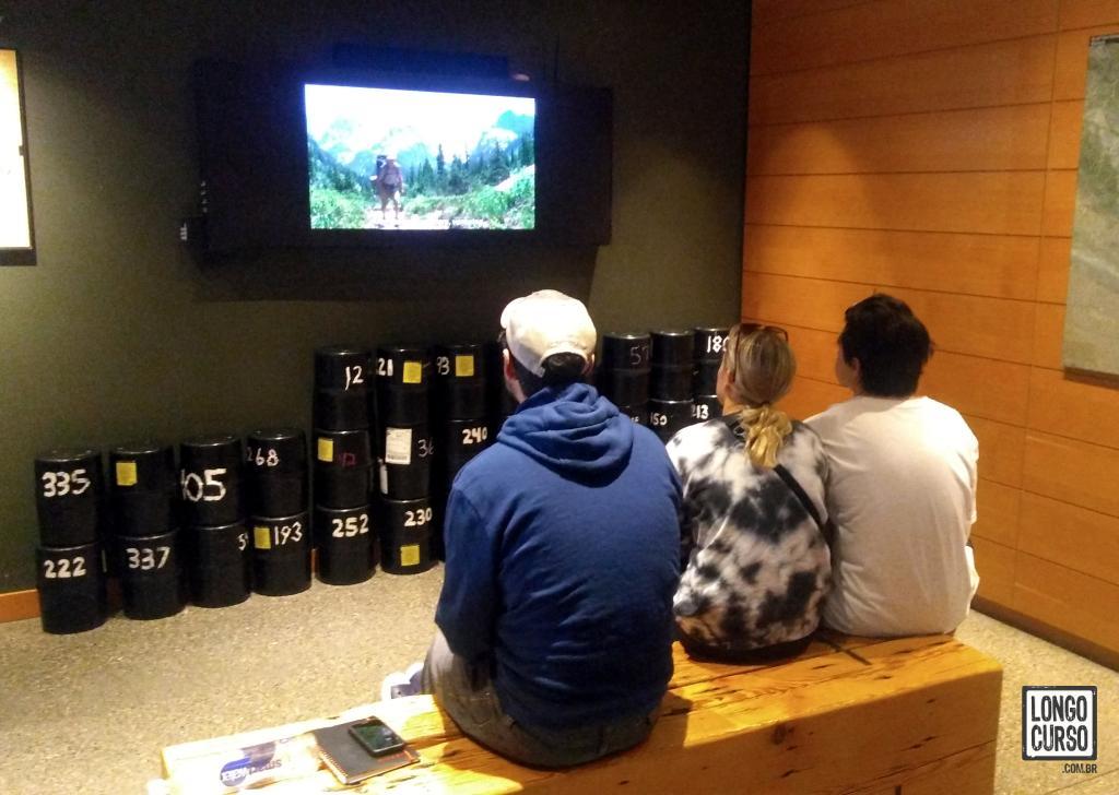 Visitantes assistem ao vídeo sobre segurança no parque antes de retirarem seus permits no Visitor Center. Ao fundo, bear canisters empilhados para empréstimo.